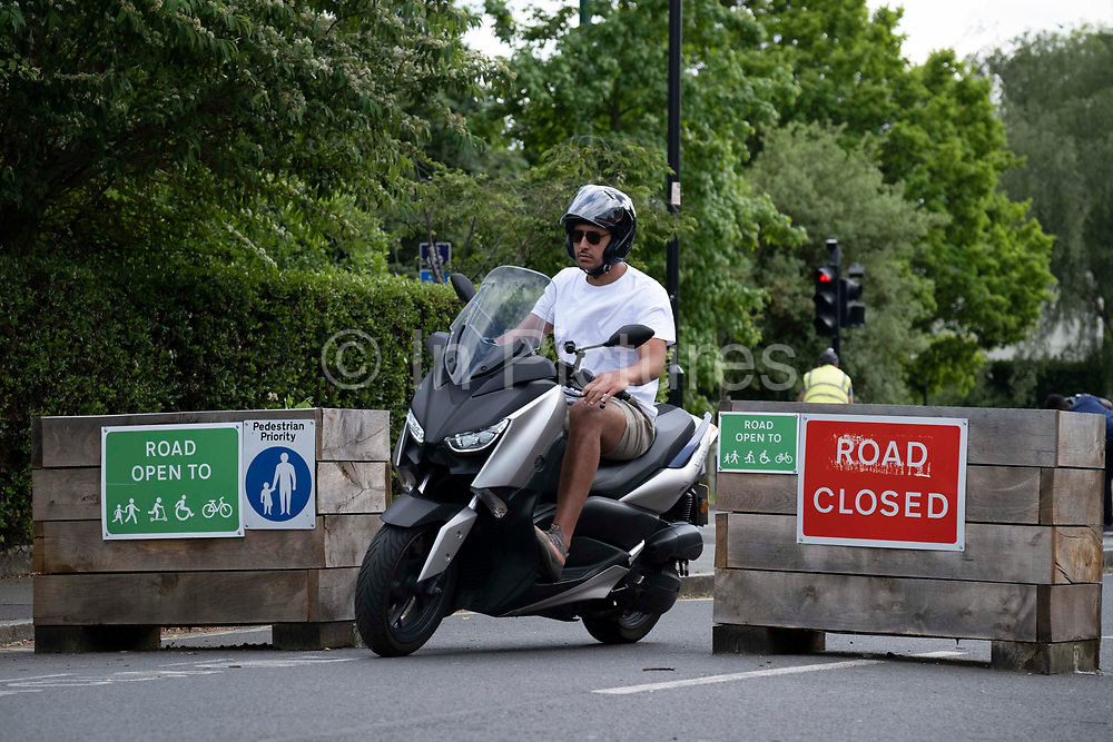 A moped rider illegally passes through the barriers that form an LTN Low Traffic Neighbourhood, an experimental closure by Southwark Council preventing motorists from accessing the junction of Carlton Avenue and Dulwich Village. Restrictions also prevent traffic from passing through at morning and afternoon rush-hour times in the borough of Southwark, on 14th June 2021, in London, England.
