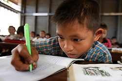Tao Aarn 9 years old does his work in a school where AusAid has funded training for minority group teachers, Ban Dakduang, Dakcheung, near Sekong, Lao PDR