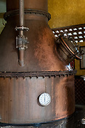 A copper still where fermented blue agave mash is turned into tequila at the Casa Siete Leguas, El Centenario tequila distillery in Atotonilco de Alto, Jalisco, Mexico. After being crushed by a stone mill the agave fibers are mixed with spring water and fermented before being distilled into tequila. The Seven Leagues tequila distillery is one of the oldest family owned distilleries and produces handcrafted tequila using traditional methods.