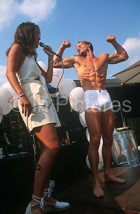 As the Mr Chelsea Body Beautiful talent competition is held on the Kings Road in London, an appreciative woman interviews a contestant. Entrants are handsome males and girls showing their muscles and well-trimmed bodies. The others have hairy chests, pectorals and biceps on-show by these young exhibitionists who parade themselves in the open-air. But this young man is smooth and sell-muscled and he holds up both arms to show his biceps and abdominals (abs) plus, unintentionally (possibly) his well-endowed private parts that are poking from within his Y-front underwear pants.