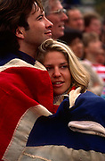 While crowds wave Union Jack flags, a young couple too young to remember a world war comfort themselves wrapped in a large union jack flag, to remember the 50th anniversary of VE (Victory in Europe) Day on 6th May 1995. In the week near the anniversary date of May 8, 1945, when the World War II Allies formally accepted the unconditional surrender of the armed forces of Germany and peace was announced to tumultuous crowds across European cities, the British still go out of their way to honour those sacrificed and the realisation that peace was once again achieved. Street parties now – as they did in 1945 – played a large part in the country's patriotic well-being.