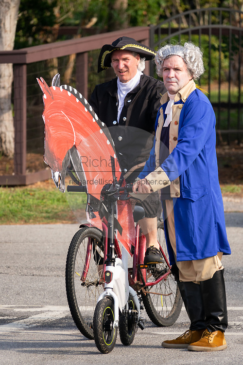 Men dressed in colonial costumes of the founding fathers ride bicycles decorated as horses during the annual Independence Day parade July 4, 2019 in Sullivan's Island, South Carolina. The tiny Sea Island beach community across from Charleston, was once a quarantine station for enslaved Africans, and is now one of the most affluent, least diverse communities with one of highest per capita real estate costs in the United States.