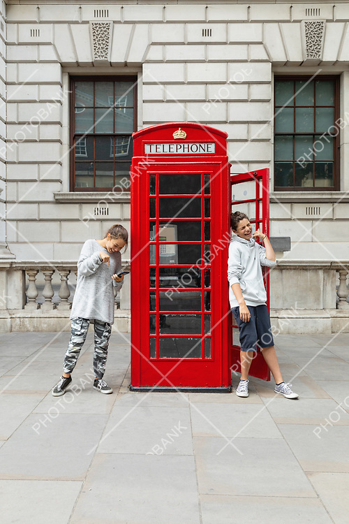 Two guys and a telephone box in London. Comic scene