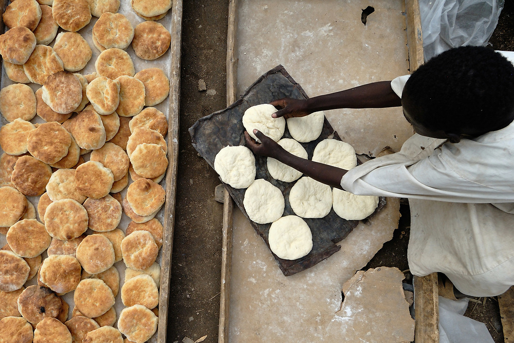 A boy arranges bread loaves in preparation for baking in the Um Labassa Camp for internally displaced persons in Sudan's wartorn Darfur province. Since 2003, as many as 400,000 people have been killed and 2,500,000 displaced by government-sanctioned violence against African farming communities in the region.