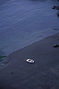 AJ02N4 Small white dinghy boat alone on dark beach Lizard Point Cornwall England. Image shot 2006. Exact date unknown.
