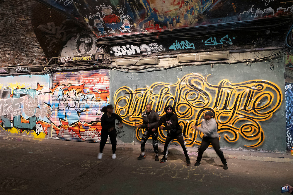 Dance crew routine beside spray painted street art and graffiti at the popular Leake Street Arches on 5th March 2021 in London, England, United Kingdom. Leake Street is a road tunnel in Lambeth, where graffiti is tolerated and encouraged regardless of the fact that it is against the law. The street is about 300 metres long, runs off York Road and under the platforms and tracks of Waterloo station.