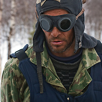 North of the Arctic Circle in Russia, nomadic Komi reindeer herder Piotr Terentév awaits arrival of the reindeer to migrate to a new camp.  His clothing and goggles come from his time performing mandatory  Russian military service.