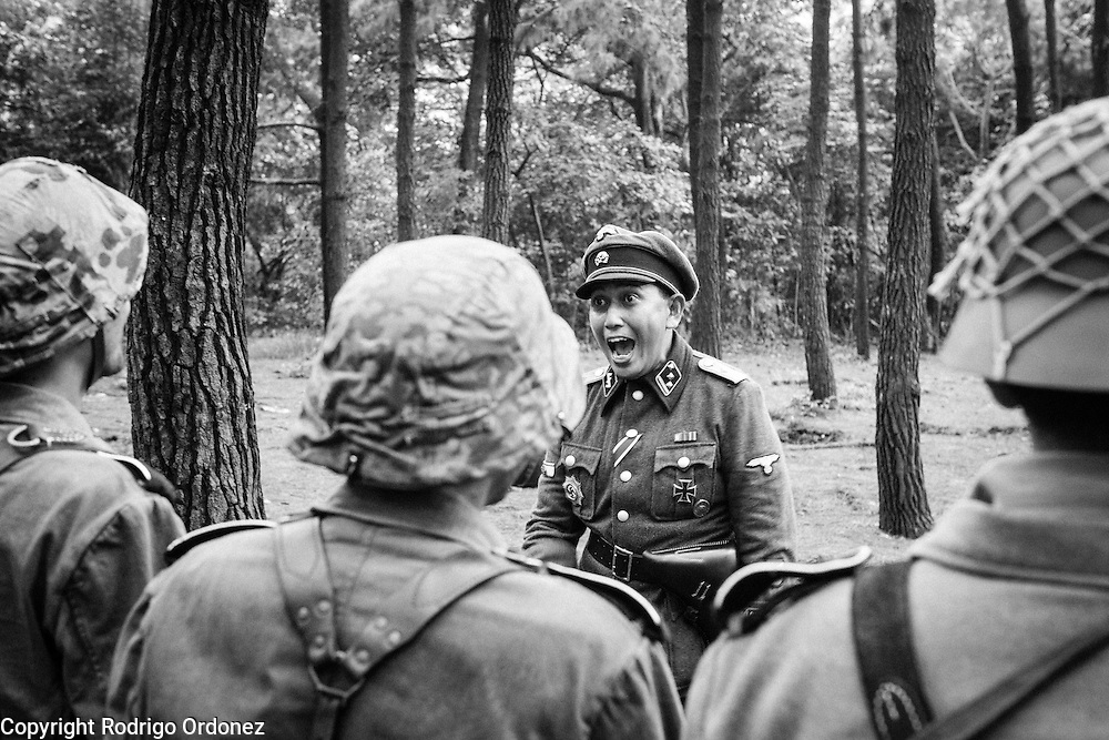 An Indonesian man dressed up as a German Waffen-SS lieutenant addresses soldiers in formation during a gathering of re-enactment enthusiasts in Cibubur, East Jakarta, Indonesia.<br /> Members of the 'Niederlande Kampfgruppe' group meet regularly to re-enact battles wearing Nazi Germany military uniforms and produce their own photos and videos. They claim that they do not do this because they identify ideologically with the Nazis, but because they are interested in World War II and military history. According to them, there is historical evidence that at least one Indonesian person was part of the 'Freiwilligen Legion Niederlande', the Dutch arm of the Waffen-SS, during World War II. Similar re-enactment groups exist in several cities across Indonesia, using the uniforms of Dutch, German and Japanese troops.