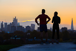 A couple enjoy the spectacular view as day breaks over London's skyline, seen from Primrose Hill, to the north of the city. London, November 13 2018.