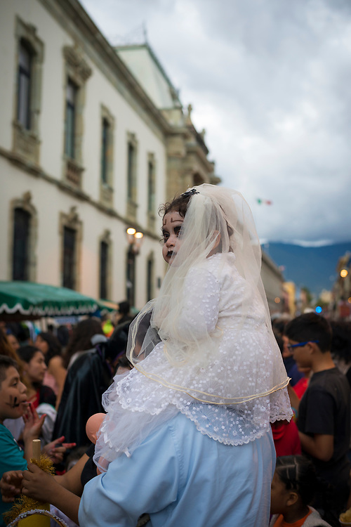A young girl sits on the shoulders of a man on a main street in the Mexican city of Oaxaca, dressed in a costume as people celebrate Day of the Dead (Día de los Muertos).