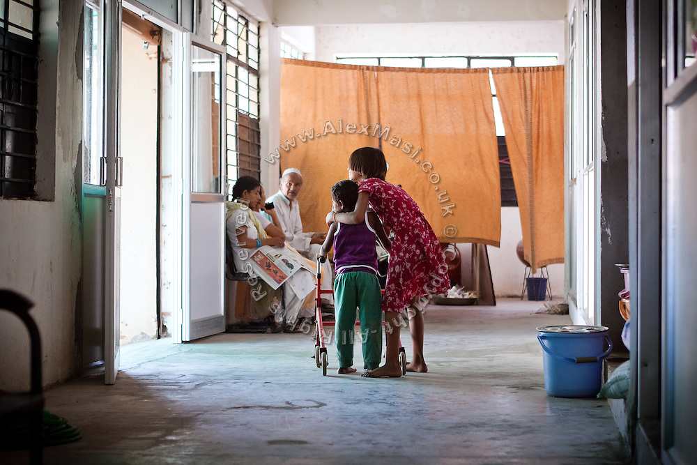 Reena, 12, is assisting her sister, Rechna, 8, a child affected by a severe neurological disorder inside Chingari Trust, the local NGO caring for disabled  children in Bhopal, Madhya Pradesh, India, near the abandoned Union Carbide (now DOW Chemical) industrial complex.