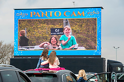 © Licensed to London News Pictures;14/04/2021; Bristol Airport, Lulsgate, UK. People in and on their cars watch a live pantomime performance of the Wizard of Oz at a drive in show at The Parking Lot Social event at Bristol Airport. The programme of entertainment is broadcast from the stage to cars by FM radio, and allows people to come to a show while still keeping people a safe social distance apart during the Covid-19 coronavirus pandemic in England. Photo credit: Simon Chapman/LNP.