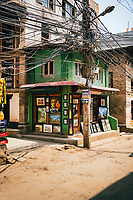A small green shophouse with wires and paintings in Patan.