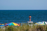 Beach goers enjoy a beautiful July day while a lifeguard keeps watch over those in the water.