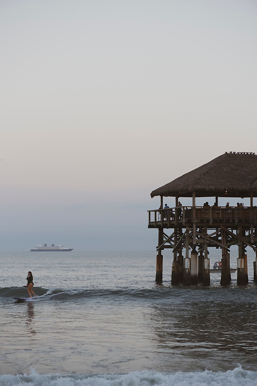 Emma Binder surfs at dusk beside the Cocoa Beach Pier in central Florida on December 15, 2020.