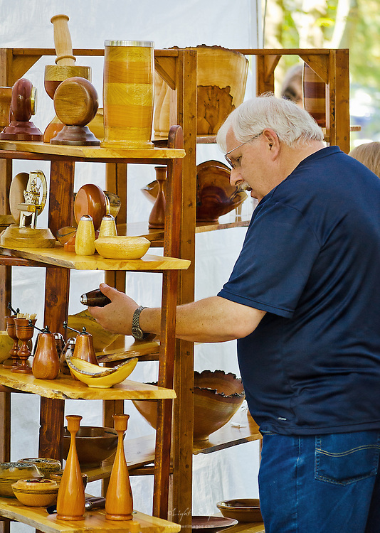 A potential customer looks over a vendor's woodworking pieces.