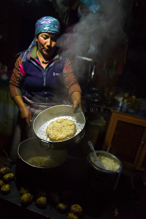 A woman prepares food in the kitchen of a trekkers lodge in Dole, Nepal. Photo © robertvansluis.com
