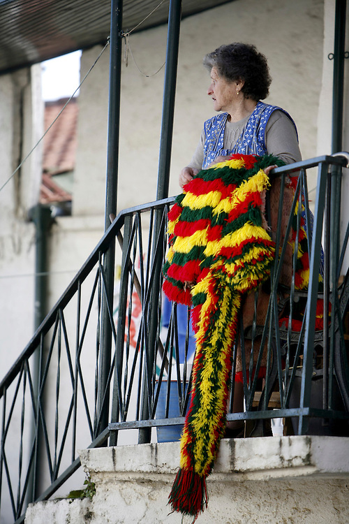 A woman on her house balcony with her son costume.  Men and boys wear a wool suit that was usually handcrafted by the owner when he was an adolescent and traditionally women were not allowed to participate.