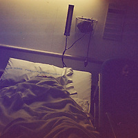 """1. When was this photo taken?<br /> <br /> 2000<br /> <br /> 2. Where was this photo taken?<br /> <br /> NY Cornell Hospital<br /> <br /> 3. Who took this photo?<br /> <br /> I did<br /> <br /> 4. What are we looking at here?<br /> <br /> My mom under the blanket in the hospital<br /> <br /> 5. How does this old photo make you feel?<br /> <br /> Mixed feelings. My mom was a tough cookie & fiercely independent. As strange as it seems, this photo makes me feel happy. I know it brought reassurance & happiness to her that I visited, was there for her, every day, during her too frequent hospital stays in her later years. At the same time I feel sad because I miss her. Although she didn't pass on until some years later, this photo seems to forebode her absence, missing her & the sadness it would bring. I also feel indebted to Lost Rolls America for offering the opportunity for me to again """"be there"""" with her.<br /> <br /> 6. Is this what you expected to see?<br /> <br /> I have absolutely no recollection of taking the photos on this roll -- even after seeing them. One half of the roll is my mom in the hospital. The other half is of extended family, including my mom, joyfully hanging out. Bottles of wine. People crashed on a couch. None of the family pictured in that half can identify where or when they were taken.<br /> <br /> 7. What kind of memories does this photo bring back?<br /> <br /> I realized that taking photos in this kind of situation serves a couple ways. It helps me focus on picture-taking -- which reduces the anxiety I might be feeling (vis-à-vis my mom's situation). It also allows me to playfully engage my mom - even if she is thumbing her nose at me in another frame taken in the hospital. Since this photo was taken before the ubiquitousness of the iPhone & digital revolution, I remember how photographing required intention: having a larger and heavier camera plus film.<br /> <br /> 8. How do you think others will respond to this photo?<br /> <br /> Feel u"""