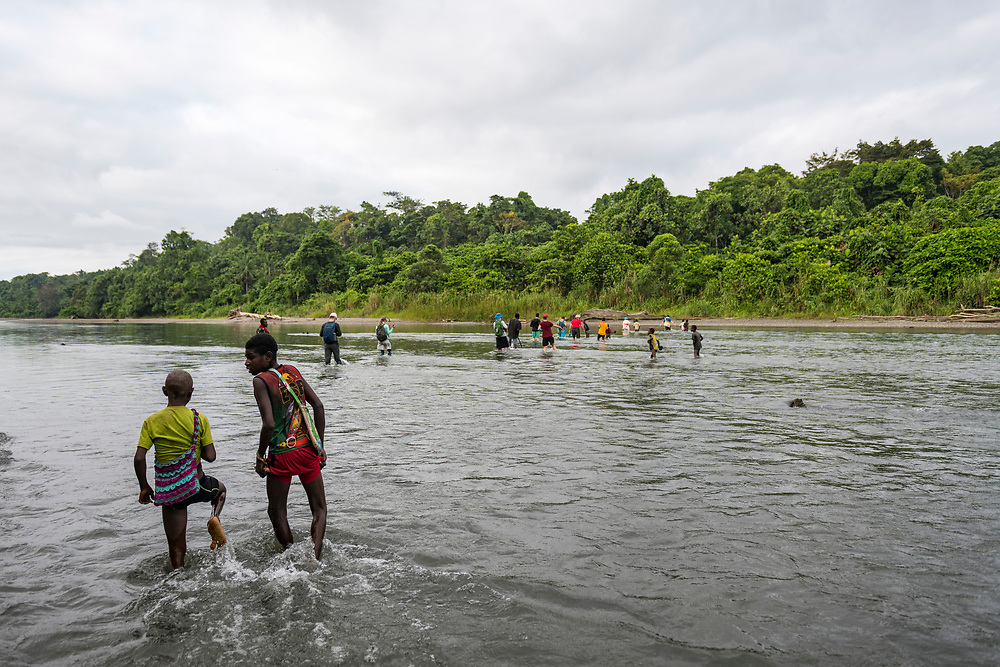 People ford the Clay River shortly after leaving the village of Likan on the one-hour hike to the A-20 Havoc crash site, located in East Sepik Province, Papua New Guinea.<br /> <br /> (June 21, 2019)