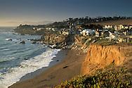Homes atop coastal cliff bluffs over ocean beach in the small coastal town of Cambria, California