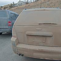 Mud covers a mini van after driving on dirt roads near Bozeman, Montana.