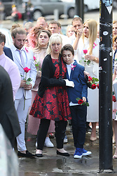 © Licensed to London News Pictures. 26/07/2017. Manchester, UK. Saffi rose's mum (red dress) Lisa arrives in manchester. The funeral of the Manchester bombing's youngest victim 8 year old Saffie Rose Roussos is taking place today at Manchester Cathedral. Saffie died when suicide bomber Salman Abedi detonated a bomb in the Manchester Arena at a Ariana Grande concert on the 22nd May 2017. Photo credit: Andrew McCaren/LNP