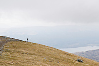 Silhouette of hiker on trail from Ben Lawers with loch Tay in distance, Scotland