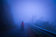 Single Minsk motorbike drives along a misty road between Dong Van and Lung Cu in Ha Giang Province, Vietnam, Southeast Asia