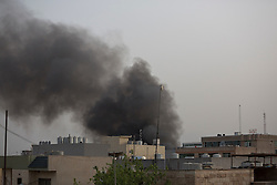 © Licensed to London News Pictures. 17/04/2015. Erbil, Iraq. Smoke rises from the site of a large explosion, which was followed by sporadic gunfire, close to the United States Consulate compound in the Iraqi Kurdish capital city of Erbil. Photo credit: Matt Cetti-Roberts/LNP