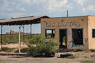 Blighted liquor store in the Permian Basin in West Texas with a salt water disposal plant on the hroizon. Despite the fracking boom there is a lot of blight a long Texas highways in the Permian Basin.