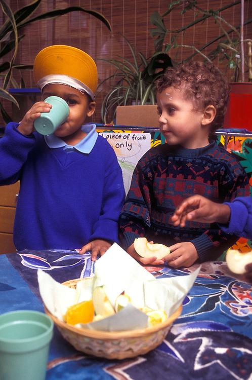 two children eating fruit at lunch break in nursery school,