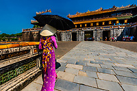 A Vietnamese woman wearing ao dai, the traditional woman's costume, approaches the Ngo Mon Gate,The Imperial City is a walled palace within the citadel of the city of Huế which is the former imperial capital of Vietnam, Hue, Vietnam.