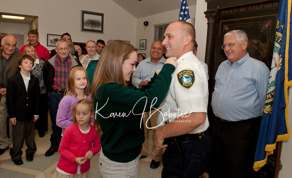 Gilford Police Chief Kevin Keenan receives his pins from his daughters Mackenzie, Carolyn and Emma after the swearing in ceremony at Gilford Town Hall Monday evening surrounded by family and friends.  (Karen Bobotas/for the Laconia Daily Sun)