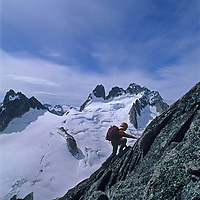 13-year old Ben Wiltsie climbs the Cain Route on Bugaboo Spire in Bugaboo Provincial Park, British Columbia, Canada.  Behind him are the Vowell Glacier, Pigeon Spire and the Howser Spire Massif