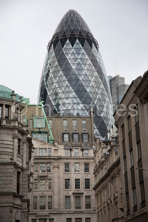 Old and new architecture in the City of London with older classical buildings and the modernism of the Gherkin at 30 St Mary Axe on 16th January 2020 in London, England, United Kingdom. This iconic building is one of the best loved buildings in London with its distinctive bullet like shape and twisted glass structure.