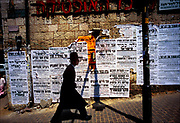 A Haredi or Ultra-Orthodox Jew in the Mea Shearim district of Jerusalem walks past death notices posted on the Old City walls.  Mea Shearim was established in 1874 outside the walls of the Old City and today remains an insular neighborhood in the heart ofJerusalem.  © Steve Raymer / National Geographic