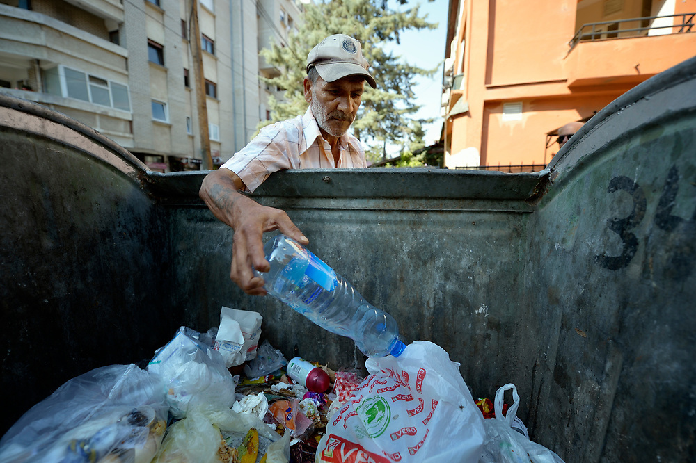 Sadedin Husein, 63, is a Roma man who lives in the mostly Roma town of Suto Orizari, Macedonia, but spends his days at work collecting plastic bottles in the streets of Skopje, which he sells to recyclers.  Here he pulls a bottle out of a garbage dumpster.