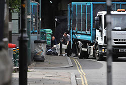 Refuge workers remove waste from a fish restaurant inside the police cordon at Borough Market following the terror attack in which eight people died.