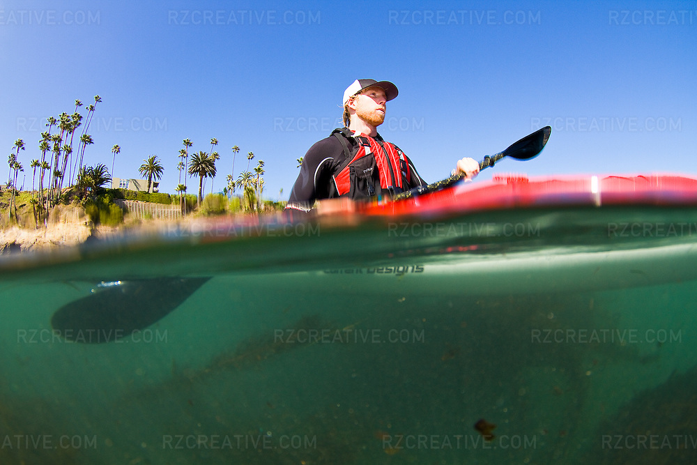Under/over water shot of a man padding a Current Designs Cypress sea kayak in the ocean.