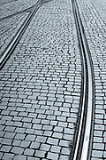 Tram rails and tiles form graphic pattern on paving stones in Porto, Portugal