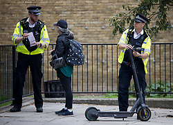 © Licensed to London News Pictures. 20/08/2021. London, UK. Police officers confiscate an e-scooter which was being ridden illegally,  during a routine operation on the Harrow Road in Maida Vale, north west London. The use of privately owned e-scooters remains illegal except for on private land. A number of rental schemes are currently being trialed across the UK. Photo credit: Ben Cawthra/LNP