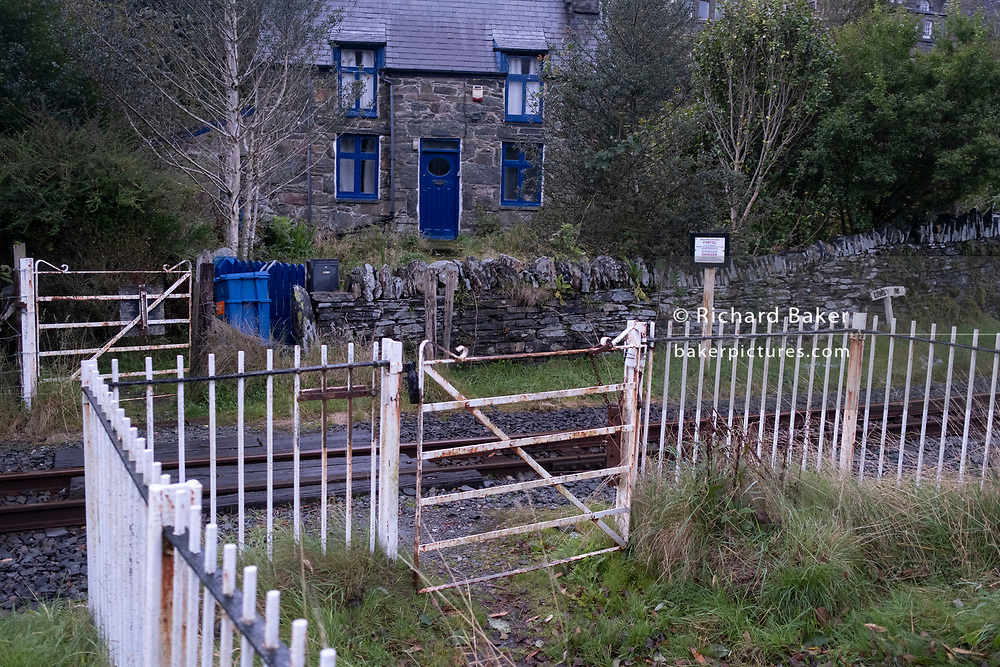 A crossing of the narrow guage railway track crossing on 3rd October 2021, in Blaenau Ffestiniog, Gwynedd, Wales. The derelict slate mines around Blaenau Ffestiniog in north Wales were awarded UNESCO World Heritage status in 2021. The industry's heyday was the 1890s when the Welsh slate industry employed approximately 17,000 workers, producing almost 500,000 tonnes of slate a year, around a third of all roofing slate used in the world in the late 19th century. Only 10% of slate was ever of good enough quality and the surrounding mountains now have slate waste and the ruined remains of machinery, workshops and shelters have changed the landscape for square miles.
