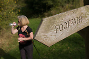 A walker drinks from a bottle next to a North Yorkshire Nationalk Park footpath sign. Pointing left, the sign tells us to follow its directions to the next village on the edge of the moors, near the village of Kilburn. The lone woman rests a short while before continuing her cross-country journey.