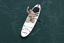 © Licensed to London News Pictures. 24/06/2021. Brighton, UK. A paddle boarder passes under Brighton pier as she enjoys the warm sunny weather. After recent rain, a period of high temperatures and sunshine is forecast in the south. Photo credit: Peter Macdiarmid/LNP