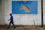 The equestrian centre of Maputo was born in the 1950 during the Portuguese Colonial time. Considered for years one of the most important place of the sub- Saharan Africa for the dressage it resisted to the colonial war and to the Mozambique civil war, his decadence started after the civil war when a poisoned batch of horse food killed most of the animal. Today the centre is trying to resume his old glory living between the past and an uncertain future. A emploee of Maputo equestrian centre passing in front of the entrance.
