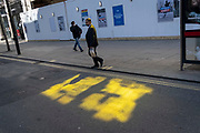 A man walks through a patch of yellow light on the ground, reflected by nearby buildings on Oxford Street, on 29th March 2021, in London, England.