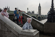 Wet tourists and visitors to London's Southbank, endure heavy summer rainfall on the steps of Westminster Bridge, England.