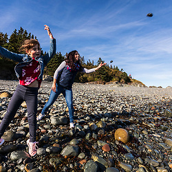 A woman and her daughter throw stones into nthe water in a cove in Quoddy Head State Park in Lubec, Maine.