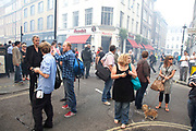 People gather on Frith Street in the smoke filled streets. A fire broke out on Dean Streen in Soho, Central London on Friday afternoon. The fire, in a five storey building in the heart of the city raged with firefighters struggling to get the blaze under control. In the nearby streets workers finishing early stood in the smoke filled streets having an end-of-the-week beer in the ghostly atmosphere.